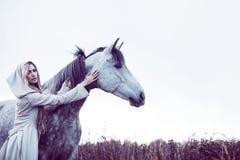 dziewczyna w kapturzastej pelerynie z koniem, skutek tonowanie obraz stock