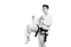 dziewczyna w karate kostiumu kimonie w studiu przy popielatym tłem Żeński dziecko pokazuje dżudo lub karate stans w bielu munduru Fotografia Stock