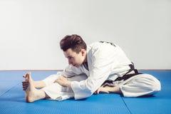 dziewczyna w karate kostiumu kimonie w studiu przy popielatym tłem Żeński dziecko pokazuje dżudo lub karate stans w bielu munduru Obrazy Stock