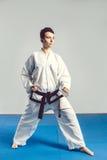 dziewczyna w karate kostiumu kimonie w studiu przy popielatym tłem Żeński dziecko pokazuje dżudo lub karate stans w bielu munduru Obraz Stock
