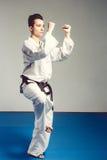 dziewczyna w karate kostiumu kimonie w studiu przy popielatym tłem Żeński dziecko pokazuje dżudo lub karate stans w bielu munduru Fotografia Royalty Free