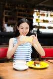 Dziewczyna w kawiarni sklepowy texting na smartphone Zdjęcia Stock