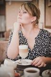 Dziewczyna w kawiarni z filiżanką kawy Obrazy Stock