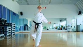 Dziewczyna w kimonie z czarnego paska przedstawieniem niektóre karate sztuczki zbiory