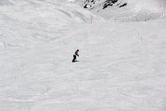 Dziewczyna w kolorowym kostiumu jest na snowboard przejażdżkach z górami fotografia stock