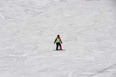 Dziewczyna w kolorowym kostiumu jest na snowboard przejażdżkach z górami zdjęcia stock