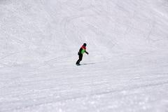 Dziewczyna w kolorowym kostiumu jest na snowboard przejażdżkach z górami zdjęcie royalty free