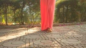 Dziewczyna w koral sukni krokach Naprzód na bruku zdjęcie wideo
