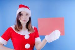 Dziewczyna w kostiumu ` Święty Mikołaj ` z znakiem na błękitnym tle Pojęcie rabaty i sprzedaże dla bożych narodzeń Rabat na holid zdjęcia royalty free