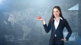 Dziewczyna w kostiumu trzyma jaskrawego wibrującego jabłka w ręce, symbolizujący nowych pomysły i świeżego styl życia w biurze po Zdjęcia Royalty Free