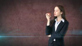 Dziewczyna w kostiumu trzyma jaskrawego wibrującego jabłka w ręce, symbolizujący nowych pomysły i świeżego styl życia w biurze po Obraz Royalty Free