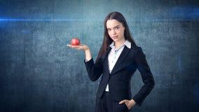 Dziewczyna w kostiumu trzyma jaskrawego wibrującego jabłka w ręce, symbolizujący nowych pomysły i świeżego styl życia w biurze po Zdjęcie Royalty Free