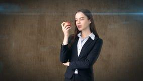Dziewczyna w kostiumu trzyma jaskrawego wibrującego jabłka w ręce, symbolizujący nowych pomysły i świeżego styl życia w biurze po Zdjęcie Stock