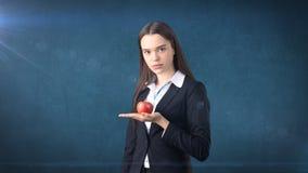 Dziewczyna w kostiumu trzyma jaskrawego wibrującego jabłka w ręce, symbolizujący nowych pomysły i świeżego styl życia w biurze po Fotografia Stock