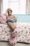 Dziewczyna W królika kostiumu I potworów kapci Czytelniczej książce Na łóżku Zdjęcie Stock