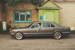 Dziewczyna w lata dziewięćdziesiąte jest o samochodach Zdjęcia Stock