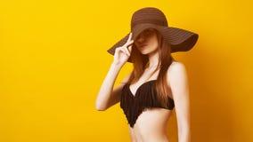 Dziewczyna w lata swimsuit i czarnym kapeluszu Czarny Piątku pojęcie Młoda zmysłowa kobieta w swimwear, odizolowywającym nad kolo zdjęcie stock