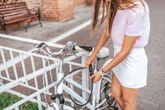 Dziewczyna w lecie w mieście, stawia kasztel na jego rowerze, ochrona przeciw kradzieży, parkuje bicykl w mieście zamyka fotografia stock