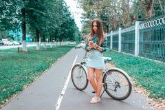 Dziewczyna w lecie w mieście, stojący obok roweru, trzyma smartphone w jej rękach, pisze wiadomości na socjalny zdjęcia royalty free