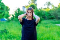 Dziewczyna w lecie w parku w czarnej koszulce azjaci piękna Zakrywa jego ucho z jego rękami Emocjonalnie głośny hałas obrazy stock
