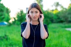 Dziewczyna w lecie w parku W czarnej przypadkowej koszulce Stawia dalej jego hełmofony posłuchaj muzyki Brunetek spojrzenia przy obraz stock