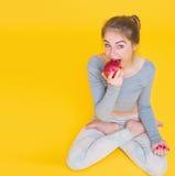 Dziewczyna w lotos pozy łasowania jabłku Zdjęcia Royalty Free