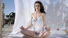 Dziewczyna w lotosowej pozyci w bungalowie na tropikalnych wyspach, relaks lato, wiatr rozwija włosianego i białego płótno, pogod zbiory