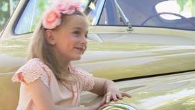 Dziewczyna w małej menchii ubiera przy retro samochodem zbiory wideo