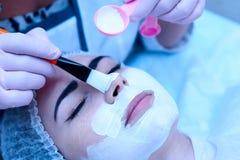 Dziewczyna w medycznej nakrętce stawia maska na jej twarzy zdjęcie stock