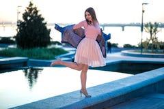 Dziewczyna w menchii sukni blisko fontanny na miasta tle zdjęcia stock