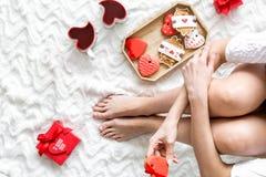 Dziewczyna w miłości z teraźniejszością, sercowatymi ciastkami i mag dla St walentynki świętowania odgórnego widoku na łóżkowym t fotografia stock