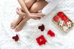 Dziewczyna w miłości z teraźniejszością, sercowatymi ciastkami i mag dla St walentynki świętowania odgórnego widoku na łóżkowym t fotografia royalty free