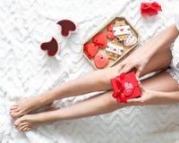 Dziewczyna w miłości z teraźniejszością, sercowatymi ciastkami i mag dla St walentynki świętowania odgórnego widoku na łóżkowym t obrazy royalty free