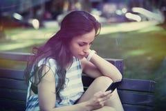 Dziewczyna w miasta parkowym używa smartphone Zdjęcia Royalty Free