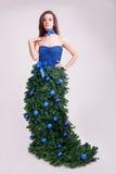 Dziewczyna w mod bożych narodzeniach ubiera pojęcie na szarym tle Zdjęcie Stock