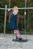 Dziewczyna w mundurek szkolny na huśtawce Fotografia Royalty Free