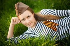 Dziewczyna w mundurze Wielka Patriotyczna wojna Wojownika obsiadanie na trawie między kwiatami Dziewczyna jest ubranym zielonych  Obraz Stock