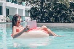 Dziewczyna w nadmuchiwanym okr?gu w basenie z laptopem poj?ciu freelancing i odtwarzaniu, obrazy stock