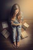 Dziewczyna w niebieskich dżinsach i szkockiej kraty koszula z długim falistego włosy siedzącym podłogowym czytaniem książkowy ret obraz stock