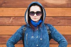 Dziewczyna w niebieskiej marynarce z kapiszonem, okulary przeciwsłoneczni, drewniany tło, patrzeją popierać kogoś, obrazy royalty free