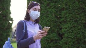 Dziewczyna w ochronnej medycznej masce na jej twarzy iść i używa telefon, wolny mo zbiory