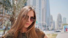 Dziewczyna w okularach przeciwsłonecznych na tle Dubaj ulicy i palm drzewa blisko twarz Strzelać w ruchu z karambolami zbiory wideo