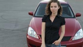Dziewczyna w okularach przeciwsłonecznych pozuje przeciw czerwonemu samochodowemu tłu zbiory wideo