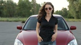 Dziewczyna w okularach przeciwsłonecznych pozuje przeciw czerwonemu samochodowemu tłu zbiory