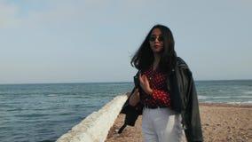 Dziewczyna w okularach przeciwsłonecznych w skórzanej kurtce chodzi przeciw tłu morze