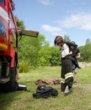 dziewczyna w palacza ` s kostiumu przeciw pożarniczemu silnikowi przygotowywa pokonywać przeszkoda kurs fotografia stock