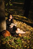 Dziewczyna w parku czyta książkę Zdjęcia Stock
