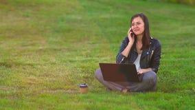 Dziewczyna w parku na gazonie pracuje na laptopie, telefonów pierścionki, odpowiada przybywającego wezwanie zdjęcie wideo