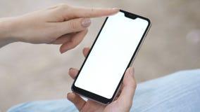Dziewczyna w parku trzyma smartphone w jej ślimacznicach i ręce wiadomość zbiory wideo