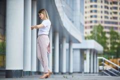 Dziewczyna w pełnych przyrostów spojrzeniach przy wristwatch blisko biznesowego budynku obraz stock